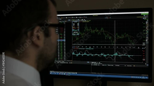 Businessman sitting and using computer showing trading graph stock exchange trading graph screen background, Business financial and forex concept. Kaliningrad - November 2017 Russian.