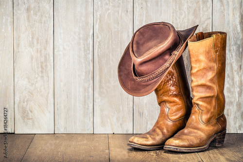 Valokuva  Wild West retro cowboy hat and pair of old leather boots on wooden floor