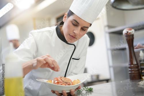 Obraz na plátně Closeup of cook chef in professional kitchen preparing dish