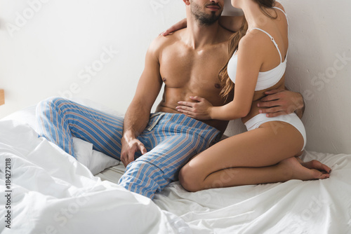 Canvastavla cropped shot of young couple in underwear sitting in bed in morning