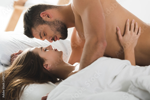 Passionate Young Couple Cuddling In Bed Morning