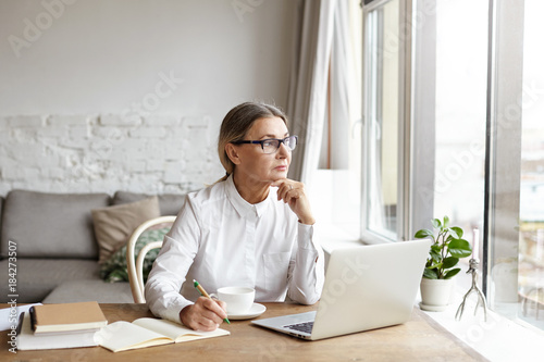 Fotografiet Attractive blonde mature female writer sitting at desk at home placing chin on h