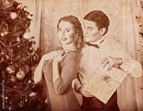 Fotografie, Obraz Christmas nostalgy couple on party near Xmas tree take gift box