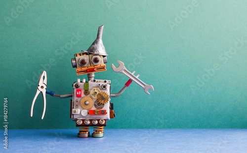 Robotic handyman pliers handwrench. Fixing maintenance concept. Creative design toy with metal funnel hopper, cogs wheels gears silver metallic body. Green wall, blue floor background. Copy space