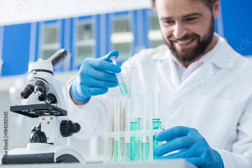 Fotografía  Delighted smart biologist holding a syringe