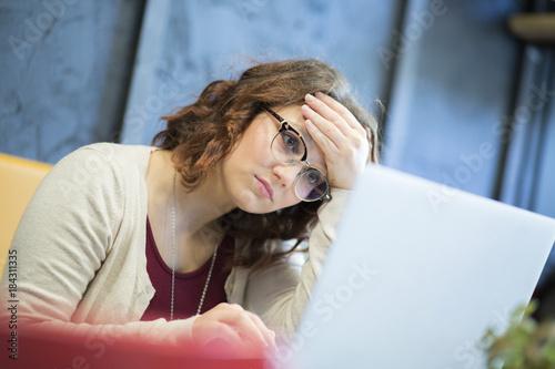 Cuadros en Lienzo Giovane studentessa con gli occhiali guarda disperata mentre sta davanti al suo