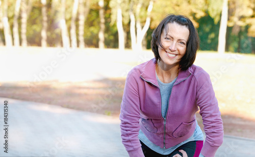Fotografia  Mature woman runner taking a rest after running in the park