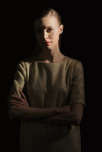 Low Key Portrait Of Girl With Crossed Hands And Half Lit Face