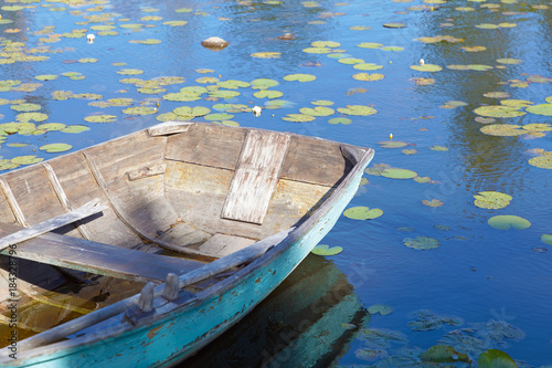 Photo Old wooden rowboat painted in wethered green color tied up
