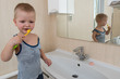 Happy boy taking bath in kitchen sink. Child playing with foam and soap bubbles in sunny bathroom with window. Little baby bathing. Water fun for kids. Hygiene and skin care for children