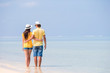 Happy family walking along the ocean on the beach