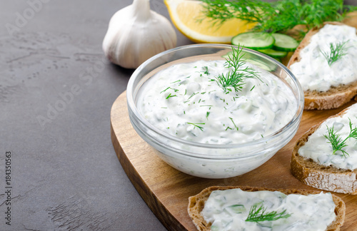 Homemade greek tzatziki sauce in a glass bowl with ingredients and sliced bread on a dark black stone background. Cucumber, lemon, dill, garlic. Close-up, horizontal, selective focus on a bowl