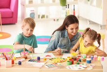 Happy Family Painting Pictures At Table Indoors