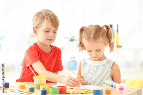 Cute children painting pictures at table indoors