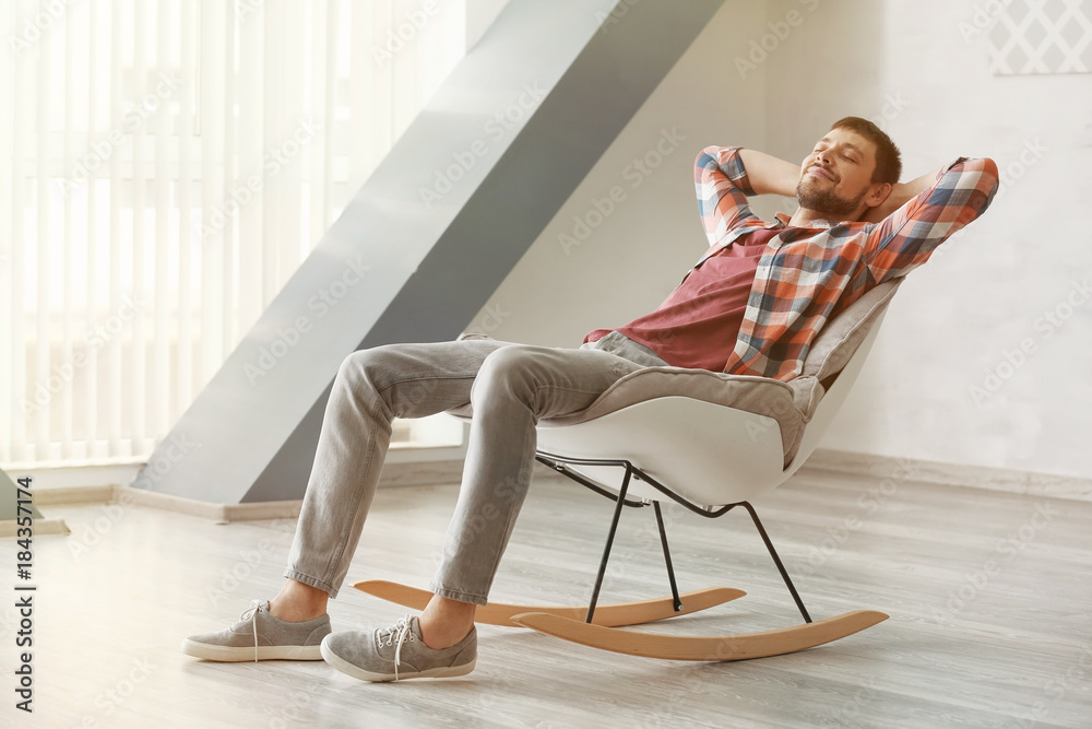 Fototapeta Handsome man relaxing in rocking-chair at home