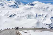 Austria, Tyrol, High Alpine Road. Snowy Scenery. Family Traveling By Motorcycle, Moving On Speed By Road Curve Of Grossglockner Hochalpenstrasse At Snowy Alps Mountains Background. Sunny May Day.