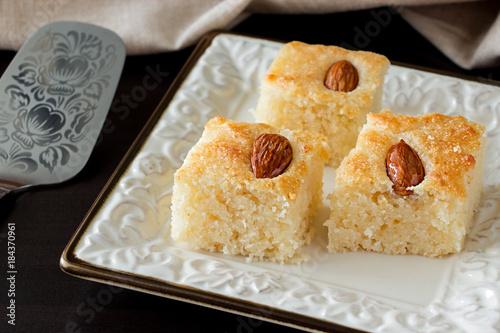 Closeup Three Pieces Basbousa Traditional Arabic Semolina Cake with Almond Nuts Orange Blossom Water. Copy space. Dark background.