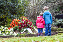Little Brother And Sister Standing At The Grave Of Their Parents