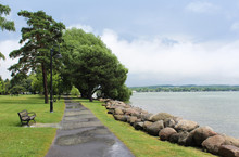 After The Rain At Canandaigua Lake. Puddles On The Sidewalk And Under The Bench. Rocks Along The Shoreline And Stormy Skies.