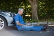 Senior man sitting by car on road