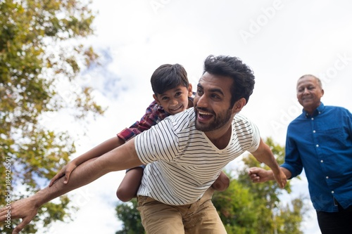 Fototapeta Happy grandfather looking at man giving piggy backing to son