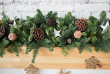 Closeup Of Details Of Green Elegant Christmas Garland Decorated With Ratten Balls, Dried Flowers Of Lotus And Wooden Stars. Horizontal Color Image.