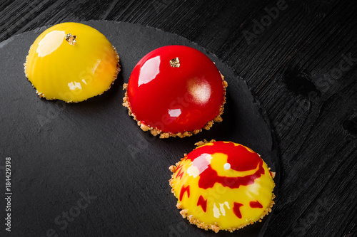 Fotografía  Beautiful cakes covered with glossy red and yellow glaze