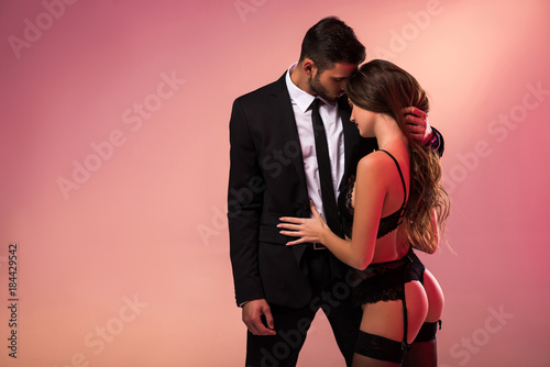 Obraz successful handsome businessman holding sexy girl in lingerie - fototapety do salonu