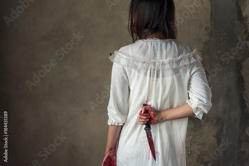 Woman holding knife back on her hand with blood Wallpaper Mural