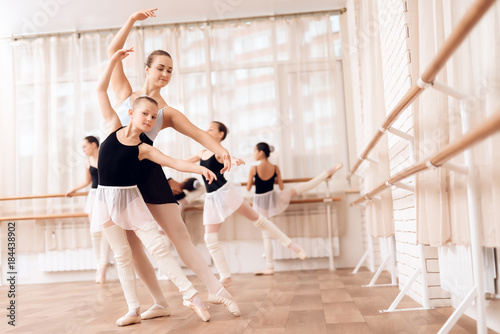 Valokuva The trainer of the ballet school helps young ballerina perform different choreographic exercises