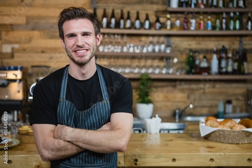 Cuadros en Lienzo Portrait of smiling waiter standing with arms crossed at counter