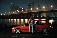 Man And His Car By The Bridge At Night.
