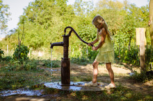 Little Child Pumping Water Fro...