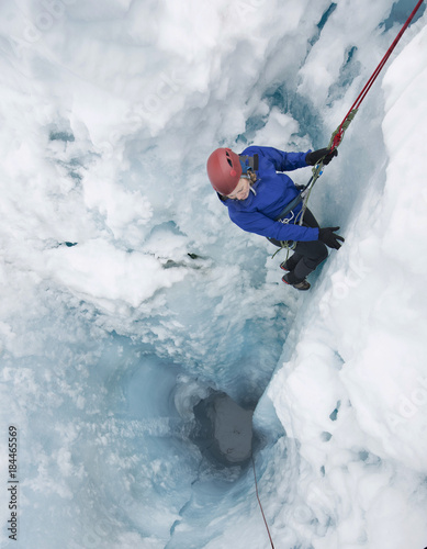 Woman rappelling into moulin on Coleman Glacier on Mount Baker, Washington State, USA