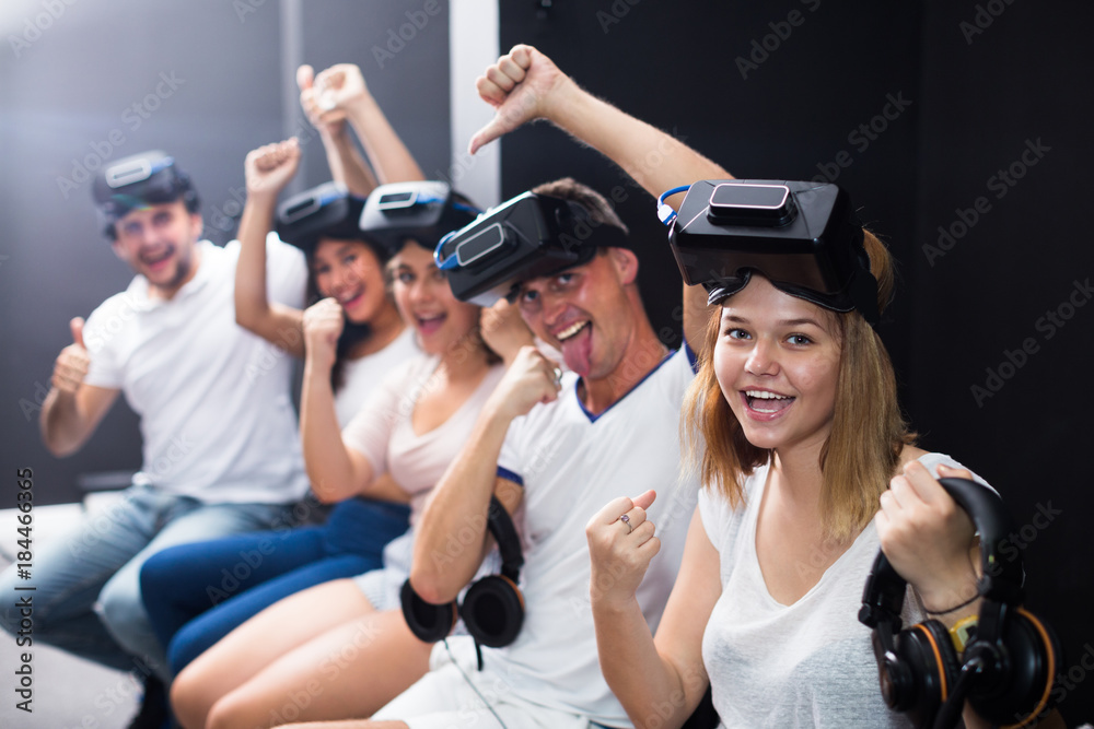 Fototapeta Group of cheerful friends are wearing virtual reality goggles