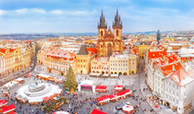 Prague In Christmas Time, Classical View On Snowy Roofs In Central Part Of City And The Christmas Market At Old Square At Background Of Tyn Church. Seasonal Winter Landscape Of Prague Cityscape.