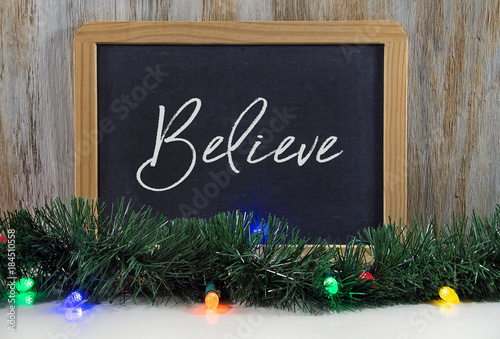 Photo  believe text in rope font design on black chalkboard with Christmas lights and g