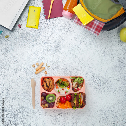 Open Lunch Box With Healthy Food Near Backpack And Laptop On