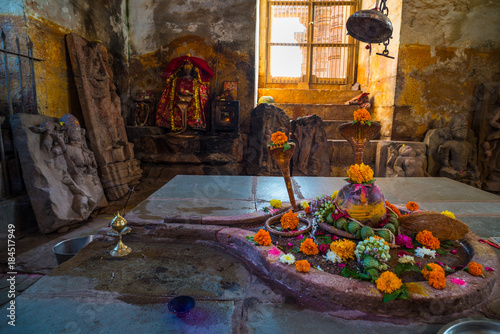 Shiva Lingam temple interior ornate with flowers and colors with majestic light coming from window, India. Architectural details of stone carvings, wide angle view.