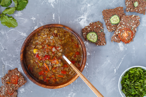 Peruvian soup with quinoa, red rice and lentils in a wooden bowl with herbs and healthy crispbread.