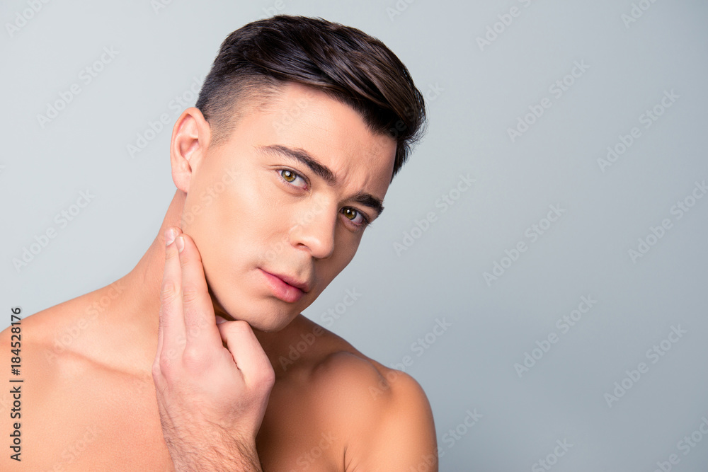 Fototapeta Close up portrait of satisfied confident handsome guy touching with shaved flawless clean soft skin after morning shaving, isolated on grey background, copy-space