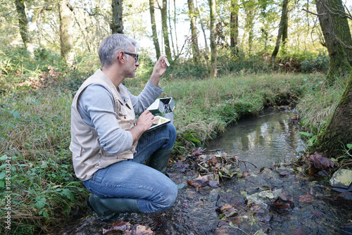 Biologist testing water quality of river Canvas Print