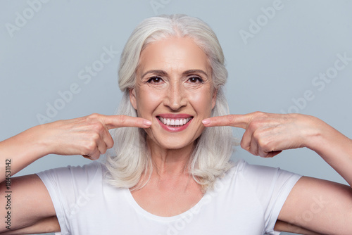 Concept of having strong healthy straight white teeth at old age. Close up portrait of happy with beaming smile female pensioner pointing on her perfect clear white teeth, isolated on gray background - 184531142