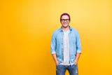 Portrait with copy space of smiling, happy guy in jeans wear, glasses, red cap holding hands in pocket, looking at camera over yellow background