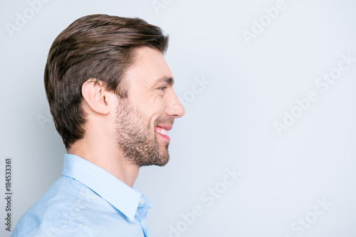 Valokuva  Close up side portrait of young, bearded, happy, smiling manager standing over g