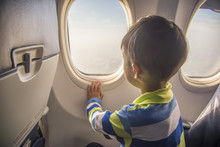 Asian Boy Looking Aerial View Of Sky And Cloud Outside Airplane Window While Sitting On Airplane Seat.