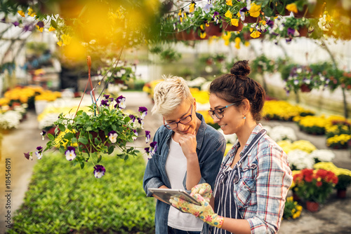 Fotografía  Adorable charming professional modern florist woman showing a list of flowers on a tablet to the curious attractive blonde female customer in a greenhouse