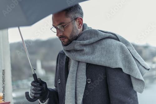 Fotografia  lonely sad man in scarf with umbrella walking under rain