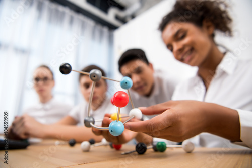 Obraz young students picking molecular model for chemistry lesson - fototapety do salonu