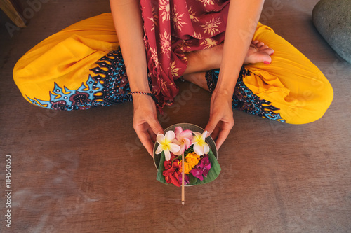 Woman holding canang sari - offering for Gods. Balinese tradition.